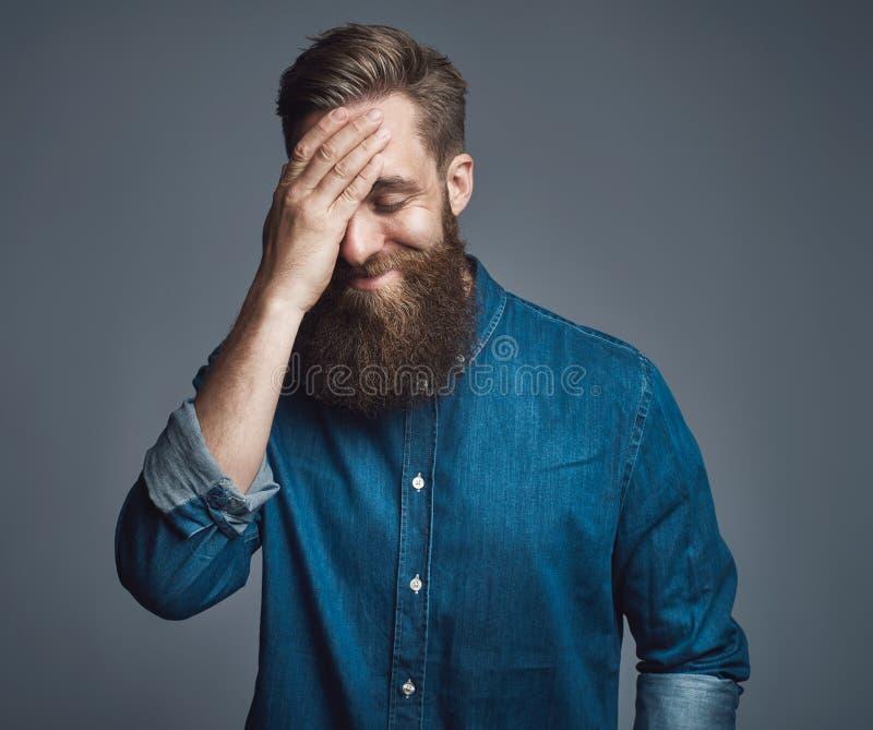 蓝色牛仔布衬衣的有胡子的人用在头的手 库存照片