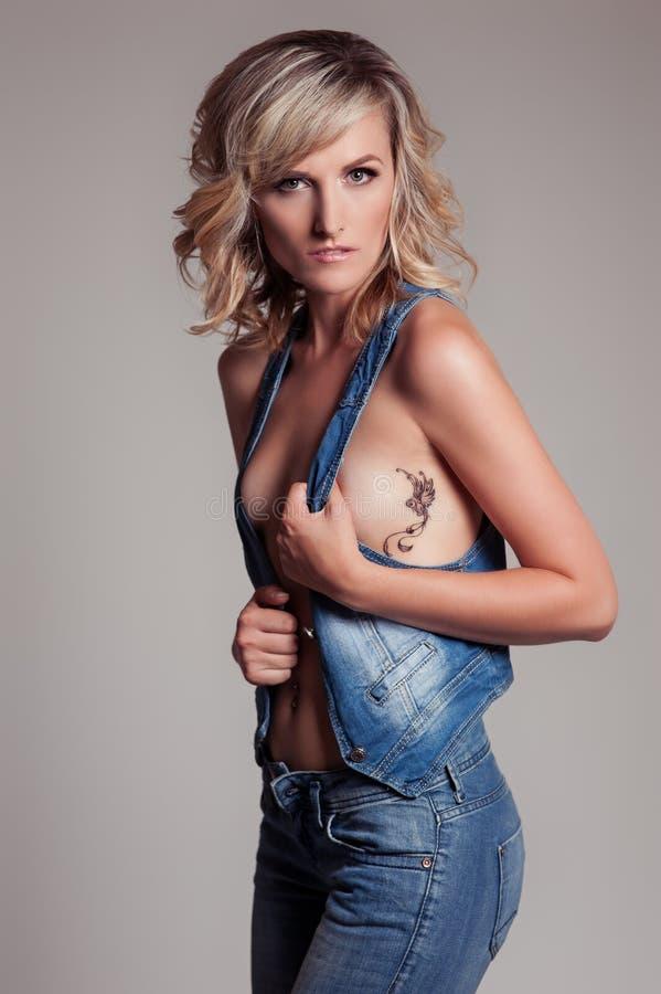 蓝色牛仔裤和一件背心的美丽的性感的妇女有在一只鸟蜂鸟一边的纹身花刺的在演播室 免版税图库摄影