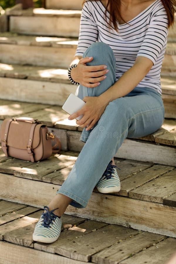 蓝色牛仔裤和镶边运动鞋的少妇坐老woode 库存图片