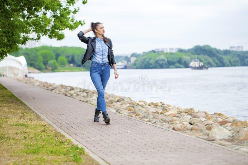 蓝色牛仔裤和黑皮夹克的年轻美丽的女孩 库存照片