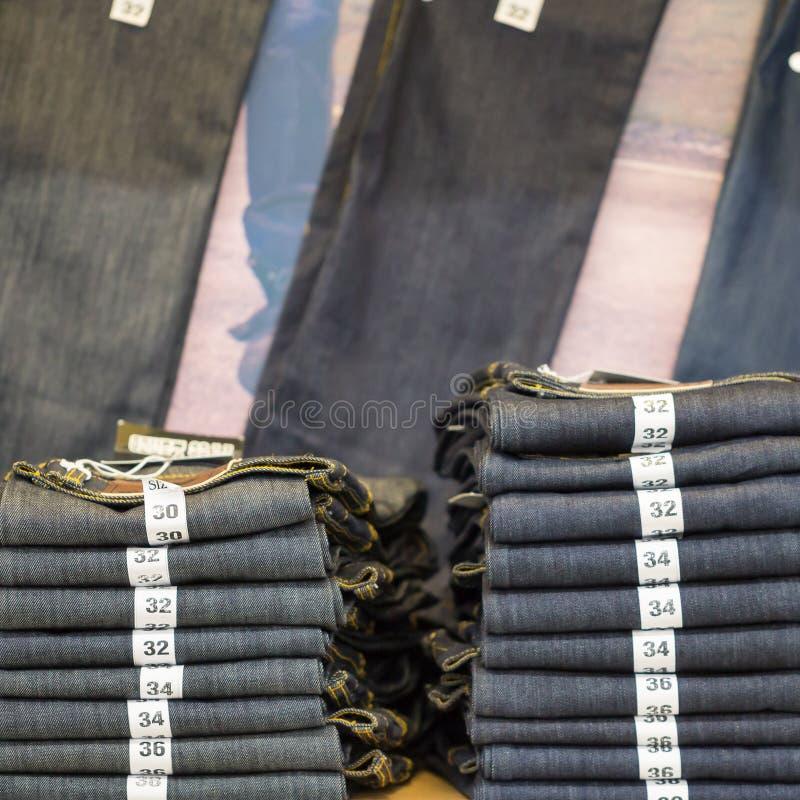 蓝色牛仔裤牛仔布汇集牛仔裤堆积与标签大小 图库摄影