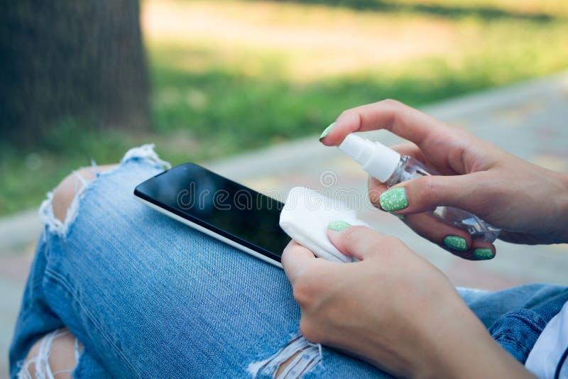 蓝色牛仔裤的妇女清洗手机抗菌抹 库存图片