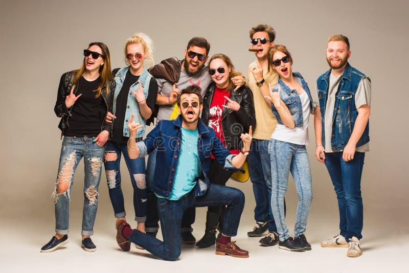 蓝色牛仔裤的愉快的年轻朋友微笑对照相机的小组反对灰色背景 免版税图库摄影