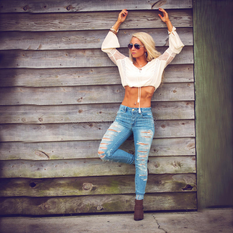 蓝色牛仔裤的白肤金发的妇女 库存图片