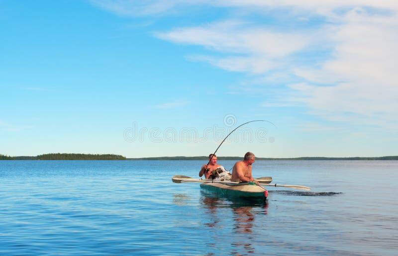 蓝色独木舟捕鱼湖 库存照片