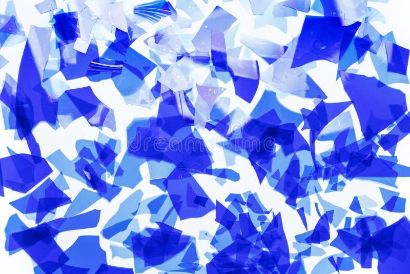 蓝色玻璃五彩纸屑 非常熔化的稀薄的色的玻璃的片段 背景图象,纹理 图库摄影