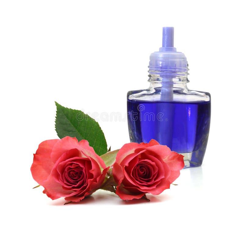 蓝色玻璃瓶精油和玫瑰色花 库存照片
