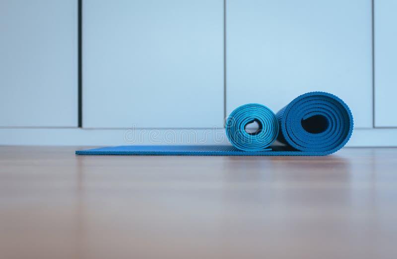 蓝色瑜伽席子一半在锻炼设备以后滚动了 免版税库存图片