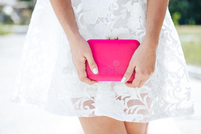 蓝色白色的女孩与桃红色袋子传动器 时尚被设置的衣裳辅助部件 库存图片