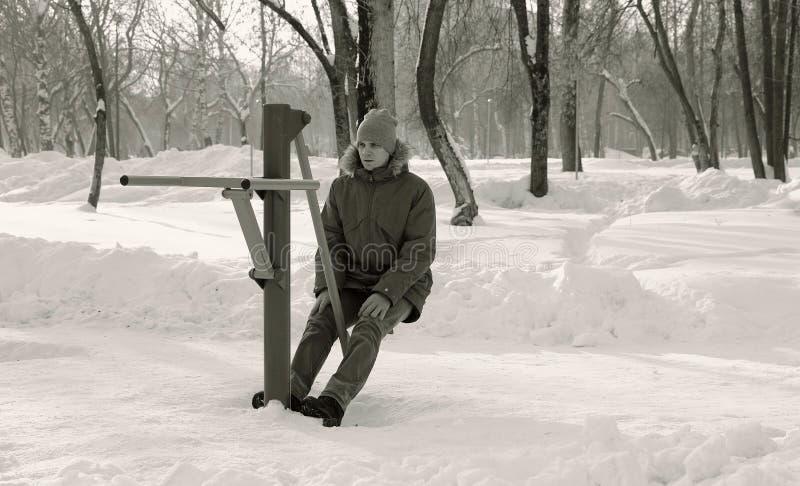 蓝色的人在有敞篷的夹克下在冬天公园做着在模拟器的腿部锻炼 正面图 黑色白色 免版税图库摄影