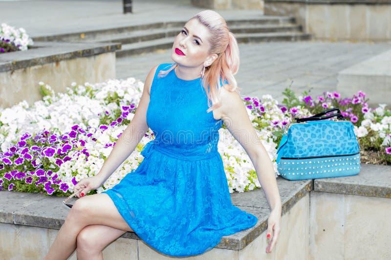 蓝色的美女在与喇叭花的花床上 免版税图库摄影