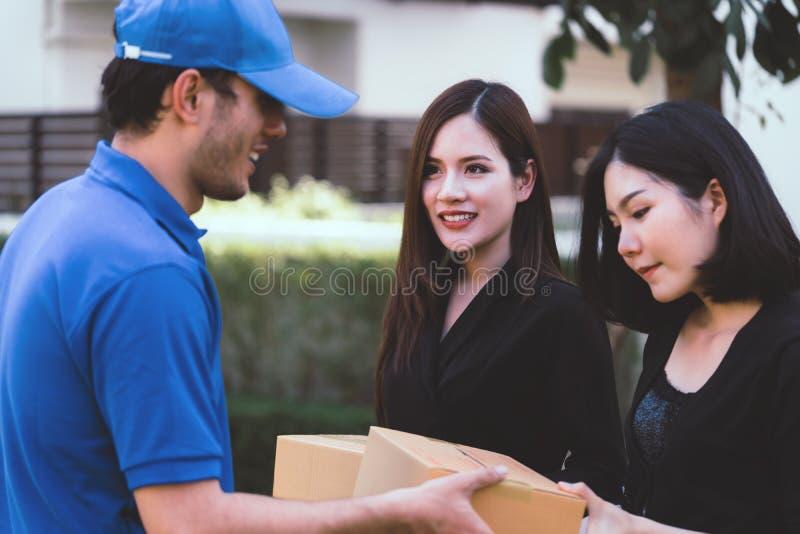蓝色的送货人递包裹的对两妇女 库存照片