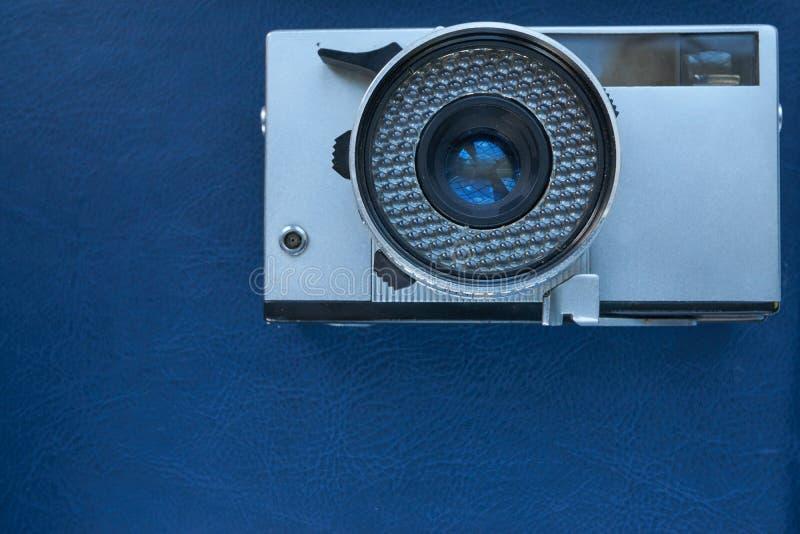 蓝色皮革表面上的减速火箭的葡萄酒照相机 库存图片