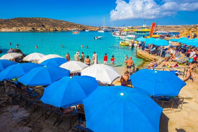 蓝色盐水湖,科米诺岛,马耳他- 2016年10月18日:游人在一个晴天拥挤享用清楚的绿松石水在伞下 免版税库存图片