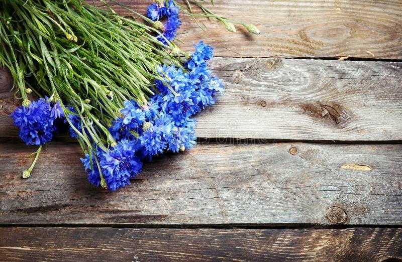 蓝色矢车菊土气花束在葡萄酒木板的 库存图片