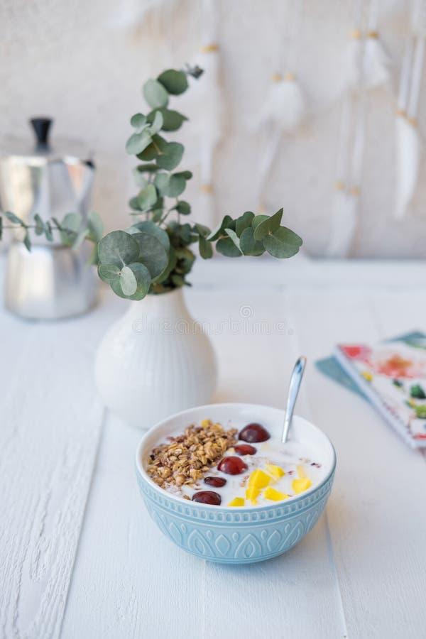 蓝色碗自创格兰诺拉麦片烘烤了用酸奶和新berrie 免版税图库摄影