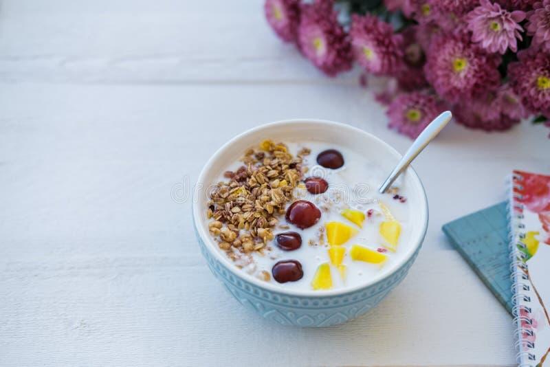 蓝色碗自创格兰诺拉麦片烘烤了用酸奶和新berrie 图库摄影