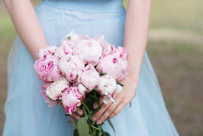 蓝色礼服举行花束的女傧相与白色和桃红色牡丹 库存图片