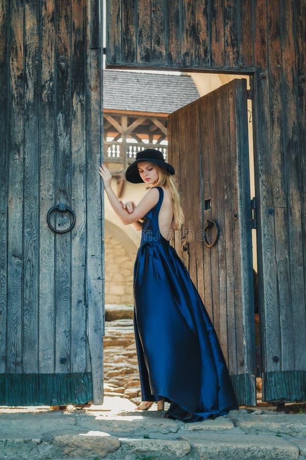 蓝色礼服和帽子的美丽的少妇 免版税图库摄影