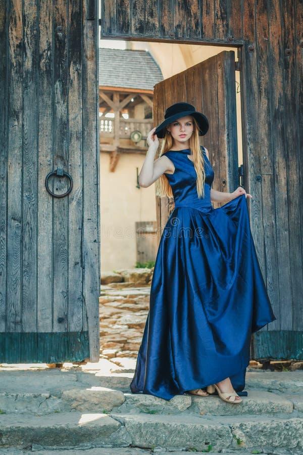 蓝色礼服和帽子的美丽的少妇 免版税库存照片