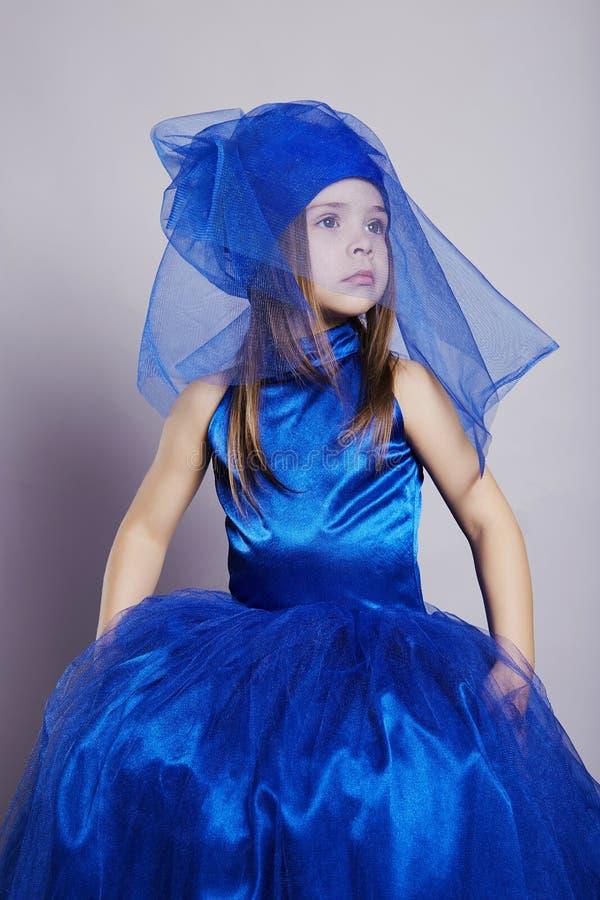 蓝色礼服和面纱的美丽的小女孩 免版税库存照片