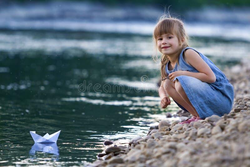 蓝色礼服的可爱的矮小的逗人喜爱的白肤金发的女孩在使用与白皮书在蓝色闪耀的bokeh w的origami小船的河岸小卵石 免版税图库摄影