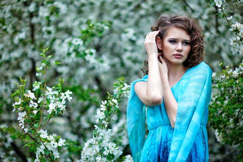 蓝色礼服的在开花苹果树中,时尚美丽的妇女 库存图片