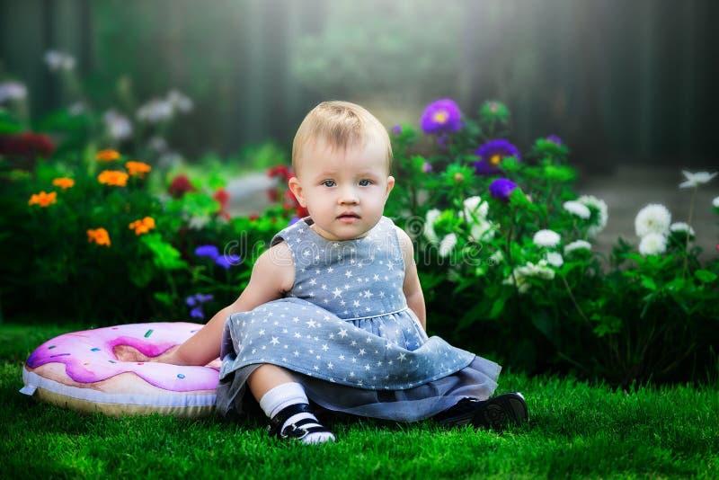 蓝色礼服的女婴坐绿草 免版税库存图片