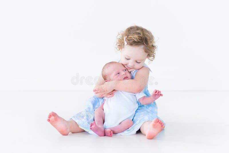 蓝色礼服的小孩女孩亲吻她新出生的兄弟的 免版税库存图片