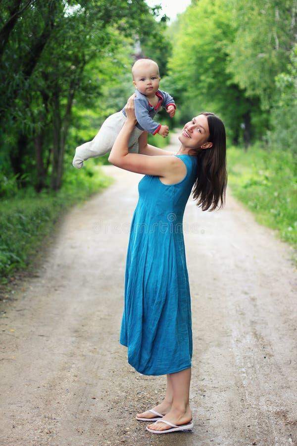 蓝色礼服的年轻母亲在她的胳膊ou中的拿着她的小儿子 图库摄影