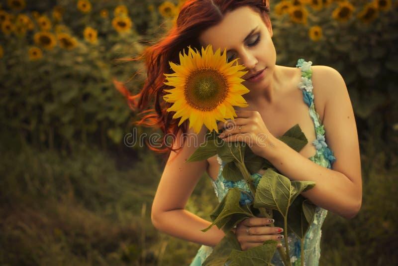 蓝色礼服的深色的白种人妇女在花的公园在拿着向日葵的夏天日落 免版税库存照片