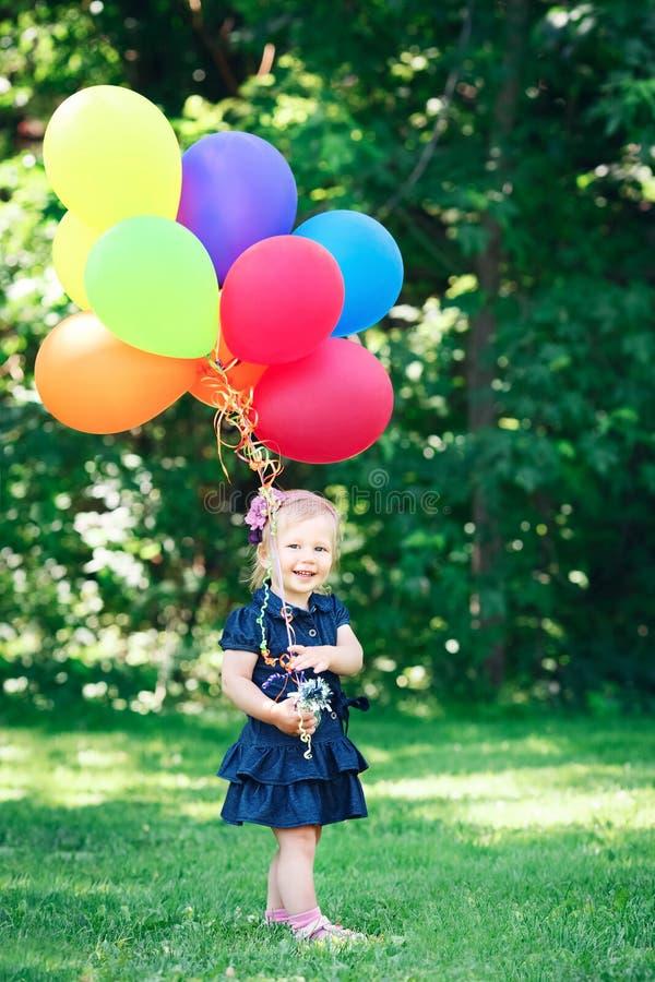 蓝色礼服的白种人女孩孩子有五颜六色的气球的,在领域草甸公园 库存照片