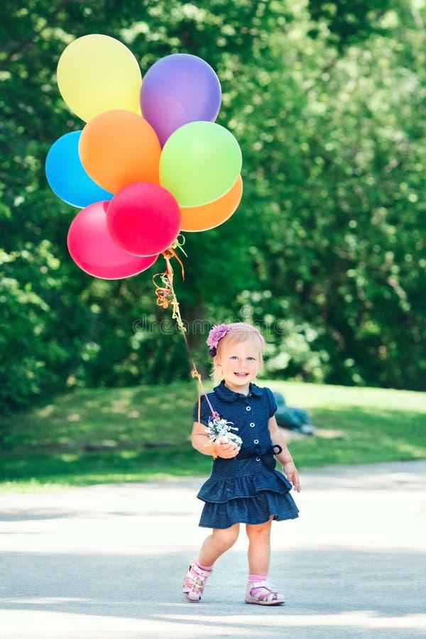 蓝色礼服的白种人女孩孩子有五颜六色的气球的,在领域草甸公园 库存图片