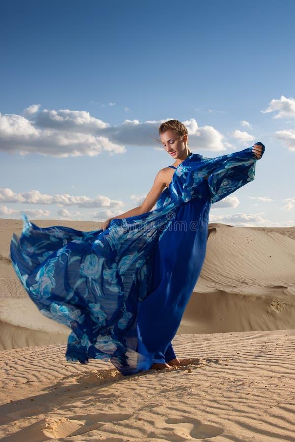 蓝色礼服的秀丽妇女在沙漠 免版税库存照片