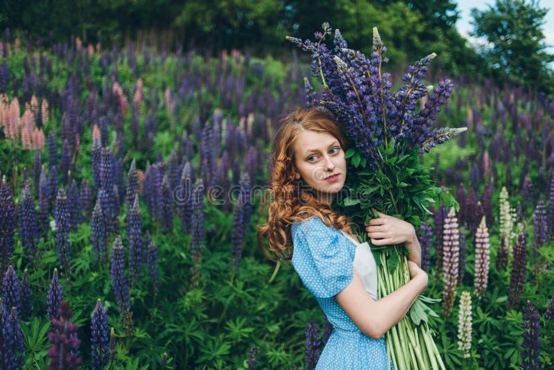 蓝色礼服的红发女孩有羽扇豆的 免版税图库摄影