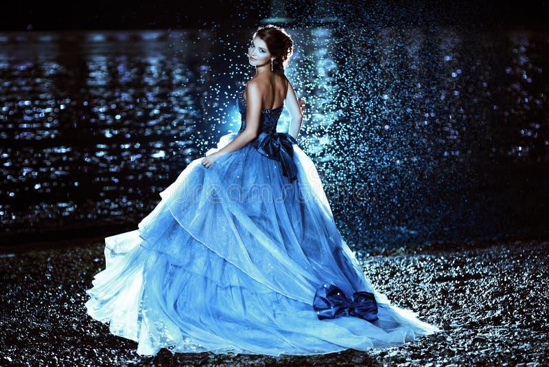 蓝色礼服的美丽的夫人 免版税库存照片