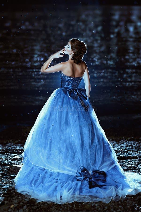 蓝色礼服的美丽的夫人 免版税图库摄影