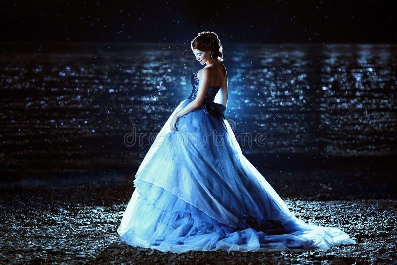 蓝色礼服的美丽的夫人 免版税库存图片