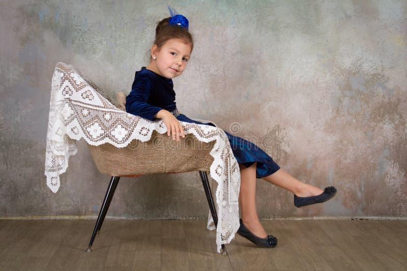 蓝色礼服的美丽的小女孩公主坐白色椅子 图库摄影