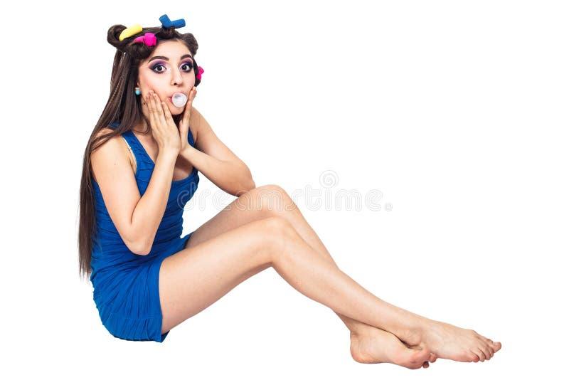 蓝色礼服的美丽的少女有卷发的人的坐地板并且嚼反刍食物 免版税库存照片