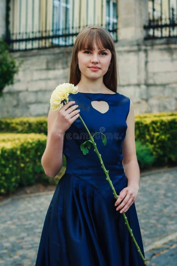 蓝色礼服的美丽的少妇拿着花 库存图片