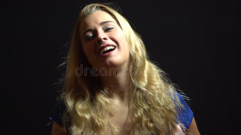 蓝色礼服的美丽的性感的白肤金发的女孩是唱歌和跳舞在演播室有黑背景 免版税库存图片