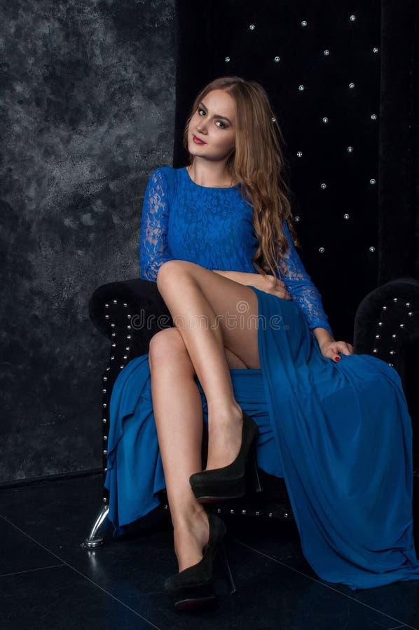 蓝色礼服的美丽的白肤金发的妇女在黑暗的内部 图库摄影