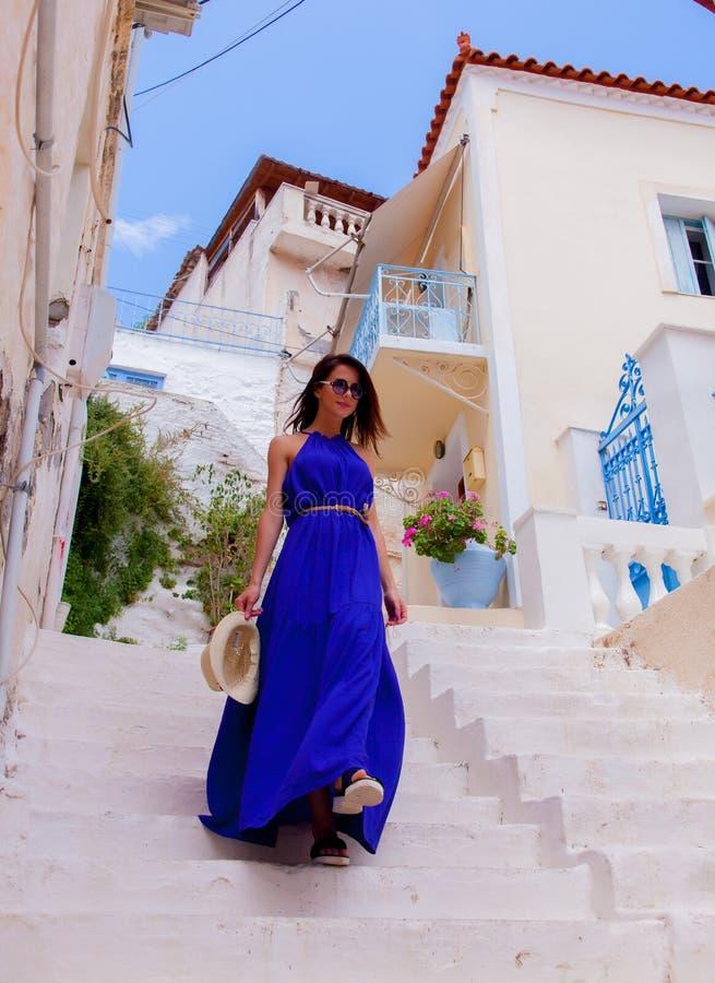 蓝色礼服的醒来年轻样式的女孩下来 免版税库存图片