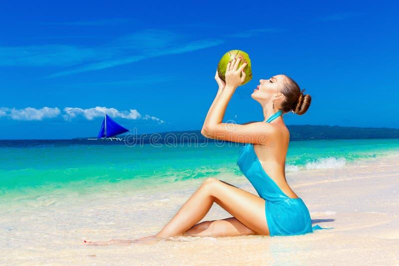 蓝色礼服的,在t的饮用的椰子水年轻美丽的妇女 库存图片