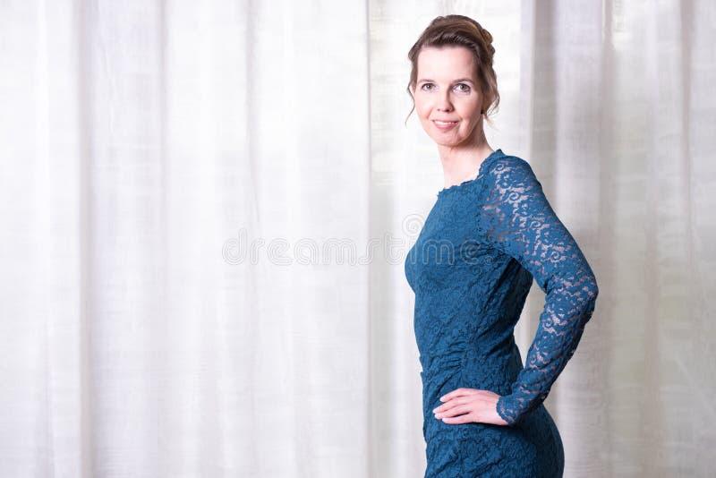 蓝色礼服的画象可爱的妇女 免版税库存图片