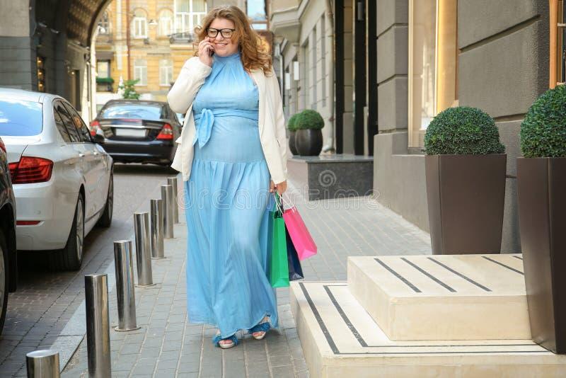 蓝色礼服谈话的美丽的超重妇女 库存图片