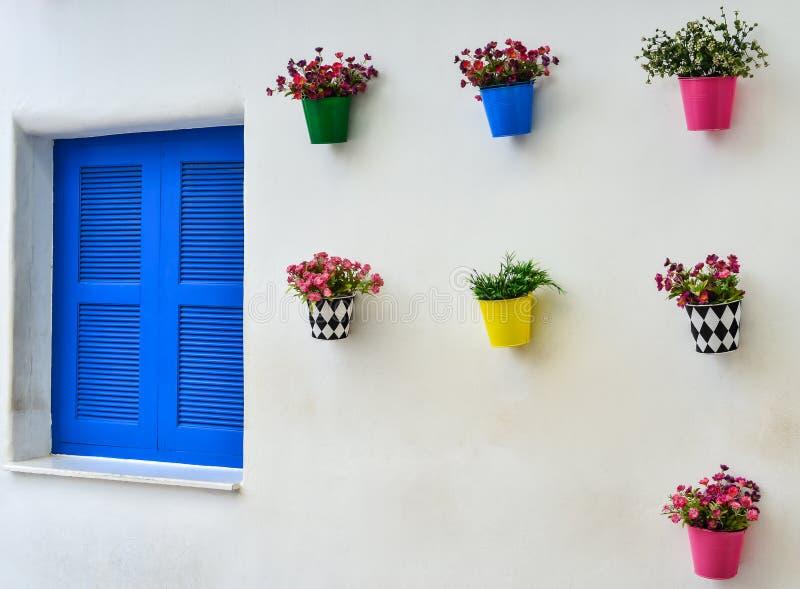 蓝色窗口和五颜六色的假花在锌花瓶 免版税库存照片