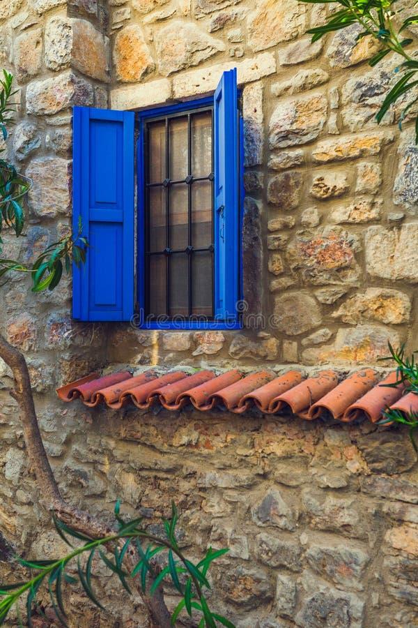 蓝色窗口在一个老石房子里 免版税库存图片