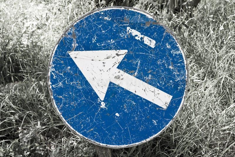 蓝色箭头签到被归档的草-概念图象 库存照片